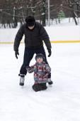 Grandfather teaches his grandchild to skate — Stockfoto