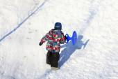 Kid climbing on a snowy hill — Stock Photo