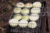 Slices of onions on barbecue grill — Stock Photo