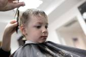 Barber cutting hair of a kid — Stock Photo