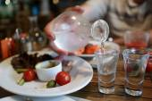 Person pouring vodka from the decanter — Stock Photo
