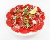 Beef carpaccio with ruccola and lemon — Stock Photo