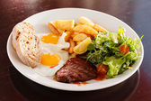 Steak with eggs and vegetables — Stock Photo