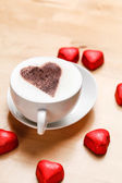 Cappuccino with heart candies — Stock Photo