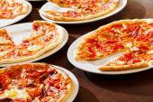 Tasty pizza on plates — Stock Photo