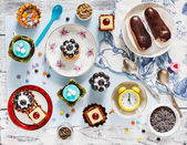 Sweets and cakes on saucers — Stock Photo