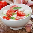 Caprese salad on white plate — Stock Photo #64996341