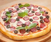 Fresh flavorful pepperoni pizza on wood — Stock Photo
