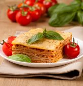 Tasty flavorful lasagna on a plate and ingredients  — Stock Photo