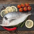 Fresh fish, lemon, spices and cherry tomatoes on a stone board — Stock Photo #69135521