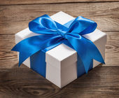 Beautiful gift box with a bow on the table from the old boards — Stock Photo