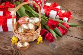 Golden Easter eggs, flowers and gifts — Stock Photo