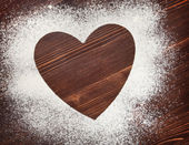 The heart of the flour on the table from the old boards — Stock Photo