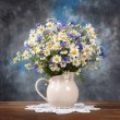 Camomile and cornflowers in a basket on table — Stock Photo #76130321