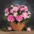 Bouquet peons in a basket on the table — Stock Photo #76130423
