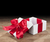 White box with a red bow on old boards — Stock Photo