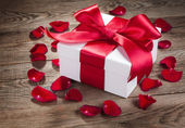 Gift box and rose petals on the old wooden boards — Stock Photo
