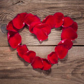 Heart of rose petals on the old wooden boards — Stock Photo