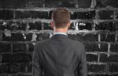 Businessman looking at brick wall — Stock Photo