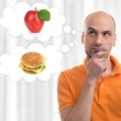 Man choosing between apple and sandwich — Stock Photo #70187499