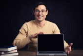 Confident young man advertising laptop — Stock Photo