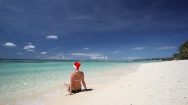 Woman in Santa Claus hat sitting on tropical beach — Stock Video