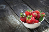 Ripe red strawberries on wooden table — Photo