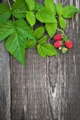 Old wooden board decorated raspberry and leaves — Foto de Stock