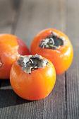 Three tasty persimmons on wooden table — Stock Photo