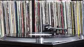 Dj turntable on vinyl background  — Stock Photo