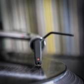 Dj stylus on spinning vinyl, record background  — Stock Photo