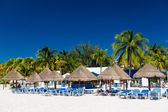 Caribbean beach with sun umbrellas and bed — Stock Photo