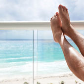 Tanning legs in hotel terrace over sea view — Stock Photo