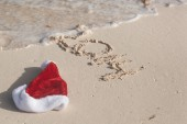 Santa Hat and 2014 numbers writing on beach — ストック写真