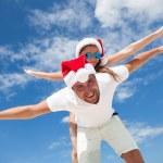Happy smiling couple piggyback together, celebrating Christmas — Stock Photo #59061065
