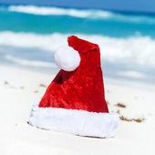 Santa Hat on white sandy beach — Stock Photo