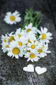 Beautiful fresh daisies decorated with hearts on wooden texture — Foto Stock