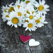 Beautiful fresh daisies decorated with hearts on wooden texture — Stock Photo