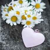 Beautiful fresh daisies decorated with hearts on wooden texture — ストック写真