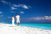 Young  beautiful newlyweds on white sandy beach — Stock Photo