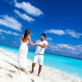 Happy newlyweds having fun on beach — Stock Photo