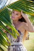 Portrait of beautiful woman behind palm frond  — Stock Photo