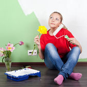 Young woman with flower and paint roller in hands  — Stock Photo