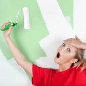 Shocked woman with paint roller in hand — Stock Photo