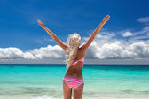 Woman in bikini with outstretched arms on tropical beach — Stock Photo