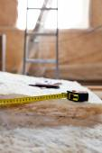 Measure tape and knife on mineral wool — Stockfoto