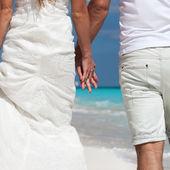 Young beautiful newlyweds on white sandy beach, rear view — 图库照片