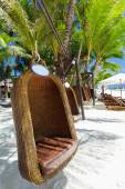 Empty hanging wicker chair on tropical beach — Stock Photo