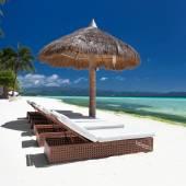 Sun umbrella and beach beds on tropical coastline — Stock Photo