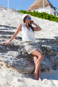 Tanned woman in sunglasses on beach — Stock Photo